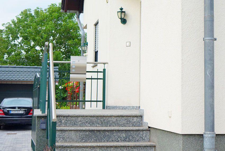 Am Treppengeländer montierte Briefkasten-Anlage mit Zeitungsfach