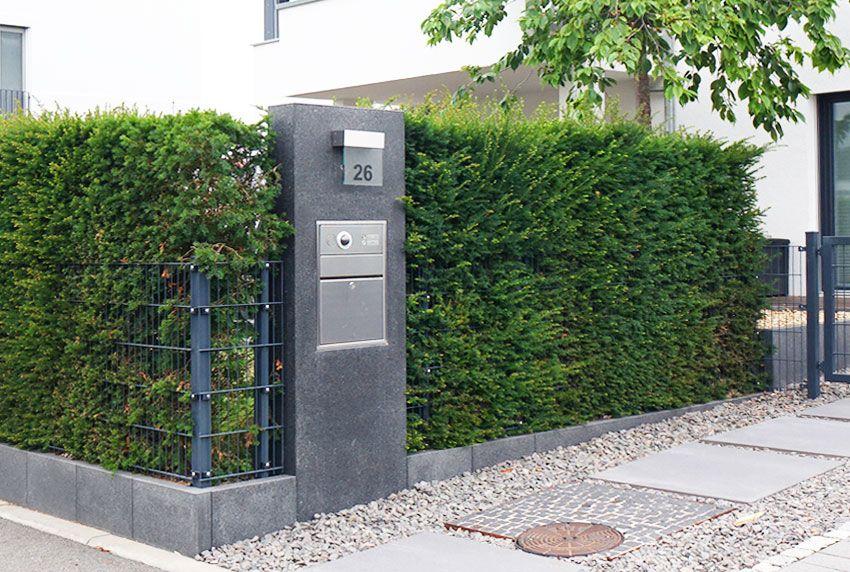 Aus Edelstahl gefertigte Briefkastenanlage mit Hausnummer in Marmorsäule kombiniert