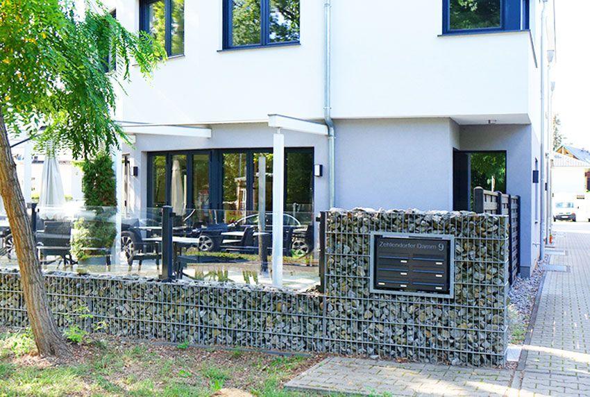 Einzelpostkästen und Briefkastenanlage in stabiler Bauart am Gabionezaun angebracht