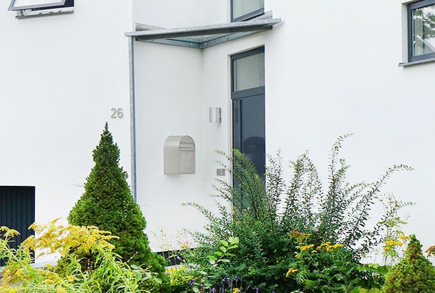 Formschönen Wandbriefkasten aus Edelstahl mit Hausnummer und Wandleuchte kombinieren