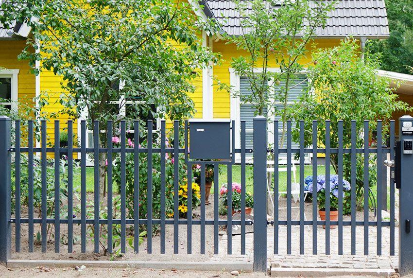Im Zaun verankerter Briefkasten mit rückseitiger Postentnahme