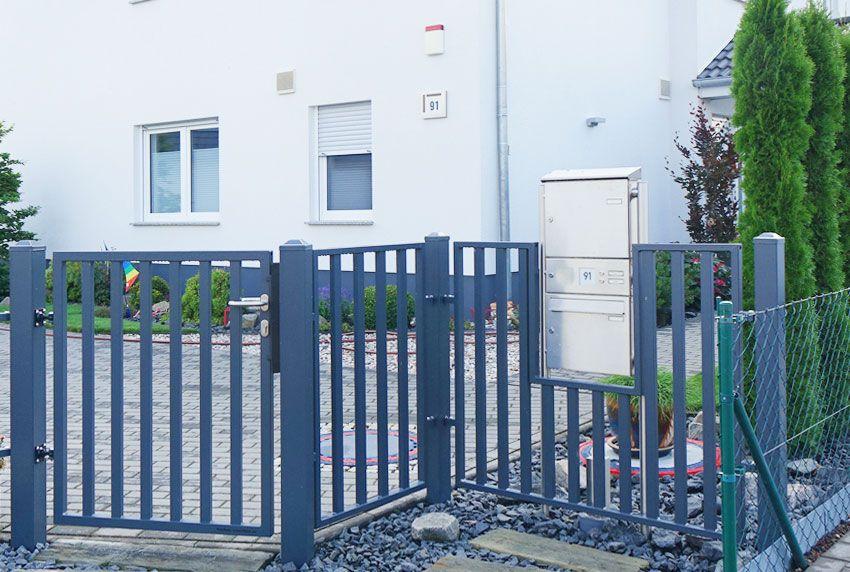 In Zaunaussparung aufgestellte Briefkastenanlage aus Edelstahl