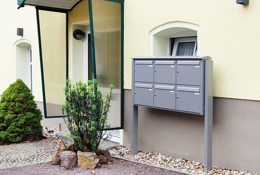 Moderne einbetonierte sechser Briefkastenanlage mit dezentem Regendach