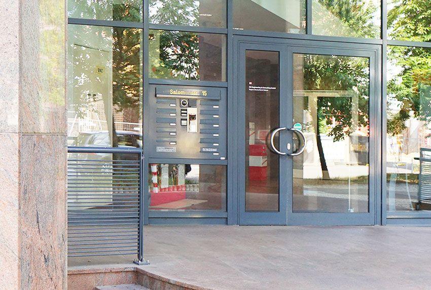 Neben Eingangstür eingelassene Briefkastenanlage mit Straßenname und Hausnummer