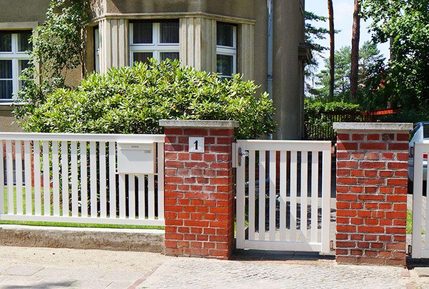 Weiße Briefkastenanlage mit einem Fach im Zaun integriert