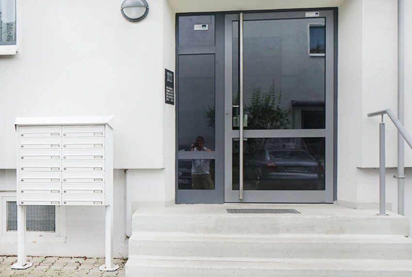 Weiße Briefkastenanlage mit vielen Postfächern