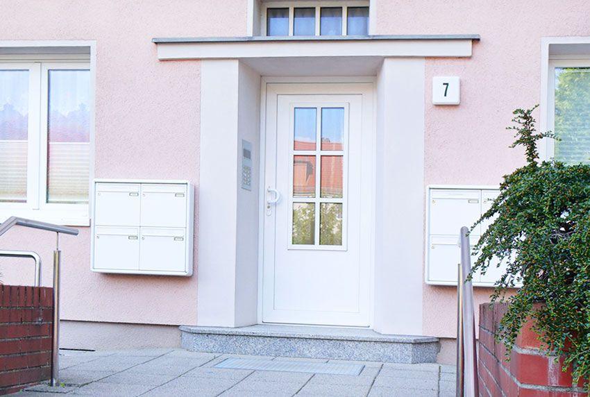 Zwei 4er-Briefkastenanlagen links und rechts am Hauseingang befestigt