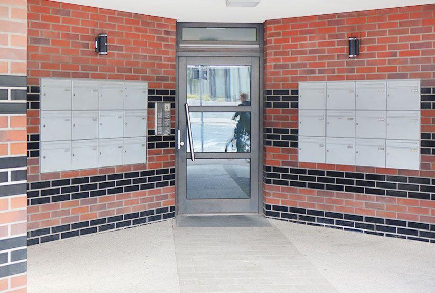Zweigeteilte Briefkastenanlage auf beiden Seiten der Tür an der Wand montiert